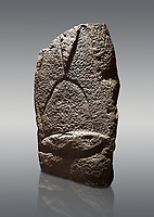 Late European Neolithic prehistoric Menhir standing stone with carvings on its face side. The representation of a stylalised male figure starts at the top with a long nose from which 2 eyebrows arch around the top of the stone. below this is a carving of a falling figure with head at the bottom and 2 curved arms encircling a body above. at the bottom is a carving of a dagger running horizontally across the menhir. Excavated from Cabamadau, Villa Sant' Antonia. Menhir Museum, Museo della Statuaria Prehistorica in Sardegna, Museum of Prehoistoric Sardinian Statues, Palazzo Aymerich, Laconi, Sardinia, Italy. Grey background.