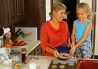 Mother and Daughter baking cookies in the kitchen having fun at home
