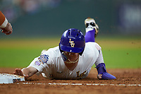 Daniel Cabrera (8) of the LSU Tigers dives head-first into first base during the game against the Texas Longhorns in game three of the 2020 Shriners Hospitals for Children College Classic at Minute Maid Park on February 28, 2020 in Houston, Texas. The Tigers defeated the Longhorns 4-3. (Brian Westerholt/Four Seam Images)
