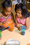 preschool Headstart 3-5 year olds nature science two girls planting bean seeds vertical