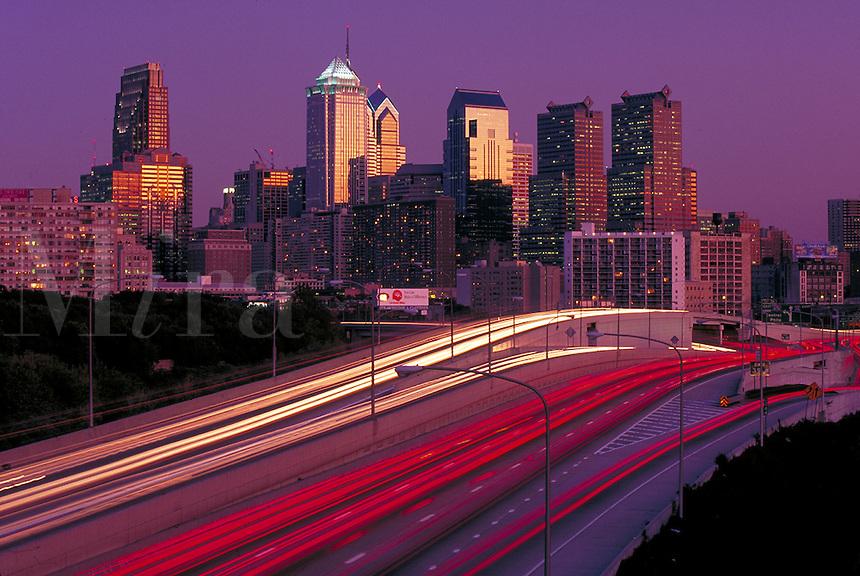 Light streaks of I 76 are the foreground of a golden sunset skyline. Philadelphia Pennsylvania United States skyline.