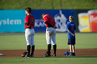 A young baseball player joins Kannapolis Intimidators infielders Grant Massey (28) and Mitch Roman (10) on the field for the National Anthem prior to the game against the Hagerstown Suns at Kannapolis Intimidators Stadium on June 15, 2017 in Kannapolis, North Carolina.  The Intimidators defeated the Suns 9-1 in game two of a double-header.  (Brian Westerholt/Four Seam Images)
