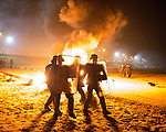 "© Joel Goodman - 07973 332324 . 23/10/2016 . Calais , France . Riot police charge residents at the Calais migrant camp known as "" The Jungle "" , in Northern France , as residents set fires , on the evening before the start of the eviction and destruction of the camp . Photo credit : Joel Goodman"