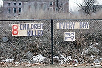 "Hand-drawn images of guns and signs reading ""8 children killed every day"" hang on a fence near an abandoned building as people take part in the March For Our Lives protest, walking from Roxbury Crossing to Boston Common, in Boston, Massachusetts, USA, on Sat., March 24, 2018, in response to recent school gun violence."