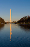 Beautiful tall tower of the Washington Monument and pond with capital building at sunset in Washington DC USA