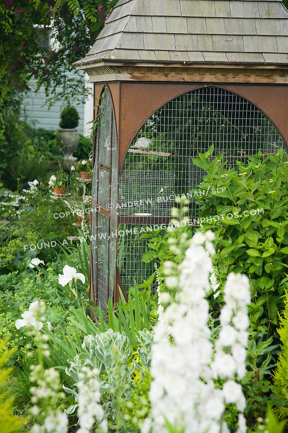 A dovecote and white dove add to the Victorian feel of the Sissinghurst-style white garden behind the late 19th c. farmhouse on this property about one hour north of Seattle in the Skagit Valley, that also includes white delphiniums, white peonies, white climbing and shrub roses, white irises, and bleeding heart, among others. Garden design by Toni Christianson, Christianson's Nursery