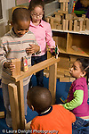 Education preschool 4 year olds block area group of children boys and girls playing with wooden human figures on top of block structure vertical