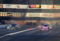 Nov 9, 2013; Pomona, CA, USA; NHRA funny car driver Courtney Force (right) races alongside Alexis DeJoria during qualifying for the Auto Club Finals at Auto Club Raceway at Pomona. Mandatory Credit: Mark J. Rebilas-