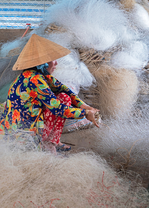 Women mending fishing Nets while the man are out fishing, this is mainly a family task. Bac Lieu,