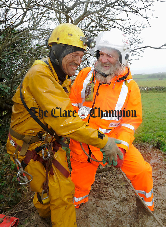 Robin Sheen, one of three cavers rescued from a cave in Doolin, is greeted by Tom Doherty of Doolin Rescue, after emerging from the cave opening. Photograph by John Kelly.