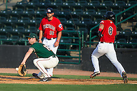 Greensboro Grasshoppers first baseman Austen Smith (18) reaches for a throw as Jose Cardona (8) of the Hickory Crawdads runs down the line at L.P. Frans Stadium on May 6, 2015 in Hickory, North Carolina.  The Crawdads defeated the Grasshoppers 1-0.  (Brian Westerholt/Four Seam Images)
