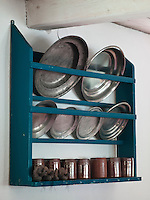 A collection of old Swedish tin plates and stoneware beakers is displayed on a rack on the dining room wall