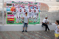 SARANSK, RUSSIA - June 25, 2018: A fan poses in front of a sign praising Iran's victory in their first game before the 2018 FIFA World Cup group stage match between Iran and Portugal at Mordovia Arena.