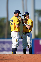 Michigan Wolverines relief pitcher William Tribucher (22) talks with shortstop Jack Blomgren (18) during a game against Army West Point on February 17, 2018 at Tradition Field in St. Lucie, Florida.  Army defeated Michigan 4-3.  (Mike Janes/Four Seam Images)