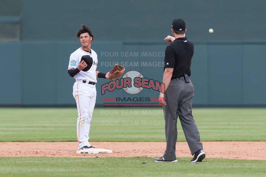 Salt River Rafters shortstop Bryson Brigman (15), of the Miami Marlins organization, reacts after being called for interference by field umpire Adam Beck during an Arizona Fall League game against the Surprise Saguaros at Salt River Fields at Talking Stick on October 23, 2018 in Scottsdale, Arizona. Salt River defeated Surprise 7-5 . (Zachary Lucy/Four Seam Images)
