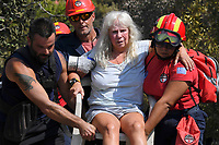 Pictured: An elderly woman is moved to safety by firemen and volunteers in the aftermath of the forest fire which has claimed dozens of lives in the Mati area of Rafina, Greece. Wednesday 25 July 2018<br /> Re: Deaths caused by wild forest fires throughout Greece.