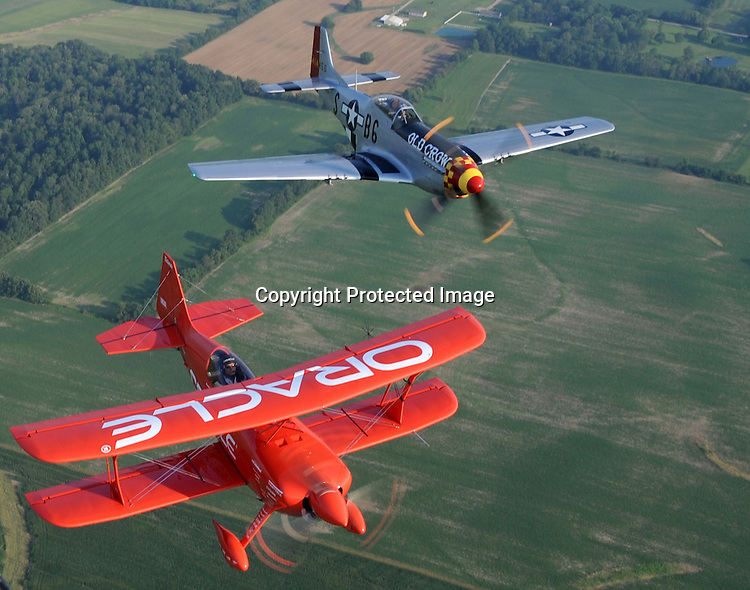 Sean D Tuckers red Oracle bi-plane flies in formation with a P51 Mustang piloted by Jim Hagedorn. The Mustang, named Old Crow, is painted in the same scheme as Col. Bud Anderson's WWII Mustang.