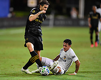 LAKE BUENA VISTA, FL - JULY 18: Cristian Pavón #10 of LA Galaxy attempts to play the ball away from Dejan Jakovic #5 of LAFC while on the ground during a game between Los Angeles Galaxy and Los Angeles FC at ESPN Wide World of Sports on July 18, 2020 in Lake Buena Vista, Florida.