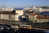 Lisbon, Portugal. Port with big ships; railway and road with busy traffic.