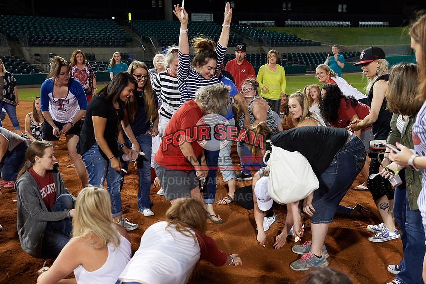 "Arkansas Travelers female fans celebrate as one fan (white hat) finds the buried diamond ring during the teams annual ""Diamond Dig"", presented by Lee Ann's Fine Jewelry, after a game against the Midland RockHounds on May 25, 2017 at Dickey-Stephens Park in Little Rock, Arkansas.  Midland defeated Arkansas 8-1.  (Mike Janes/Four Seam Images)"