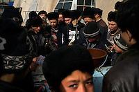 Uighur men gather around a streetside snack vendor in the Sunday Market in the Grand Bazaar in Kashgar, Xinjiang, China.