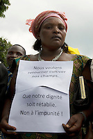 In the Mugunga I IDP (Internally Displaced Persons) camp, a woman attends a demonstration organised by the women's group SAUTI (Sauti ya Mwanamke Mkongomani), which means Voices of the Women of Congo. Her placard reads, 'We want to return to our land to cultivate our fields. Restore our dignity. No to impunity.'