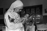"""Calcutta, India. April 04, 1975.<br /> Mother Teresa in her orphanage spending time with kid. She takes long hours in the morning to talk and confront them.  Mother Teresa (Agnes Gonxha Boyaxihu) the Roman Catholic, Albanian nun revered as India's """"Saint of the Slums,"""" was awarded the 1979 Nobel Peace Prize."""