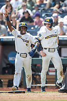 Michigan Wolverines second baseman Ako Thomas (4) celebrates at the plate with teammate Jack Blomgren (2) during Game 11 of the NCAA College World Series against the Texas Tech Red Raiders on June 21, 2019 at TD Ameritrade Park in Omaha, Nebraska. Michigan defeated Texas Tech 15-3 and is headed to the CWS Finals. (Andrew Woolley/Four Seam Images)