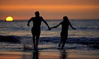 Happy couple on vacation enjoying the sunset running on the beach