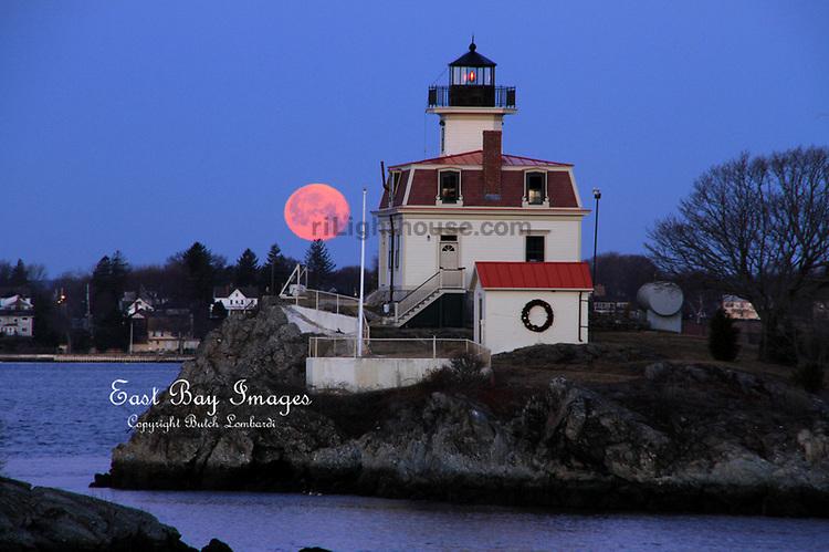 The full moon setting behind Pomham Rocks Lighthouse, Narragansett Bay RI.