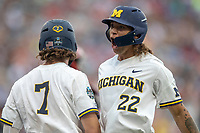 Michigan Wolverines outfielder Jordan Brewer (22) celebrates with teammate Jesse Franklin (7) after scoring a run during Game 1 of the NCAA College World Series against the Texas Tech Red Raiders on June 15, 2019 at TD Ameritrade Park in Omaha, Nebraska. Michigan defeated Texas Tech 5-3. (Andrew Woolley/Four Seam Images)