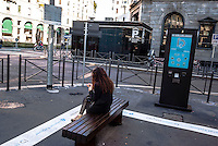 Milano, Isola digitale. Totem multimediale a schermo tattile e panchine. Donna con capelli rossi --- Milan, digital area. Multimedia touchscreen totem and benches. Woman with red hair