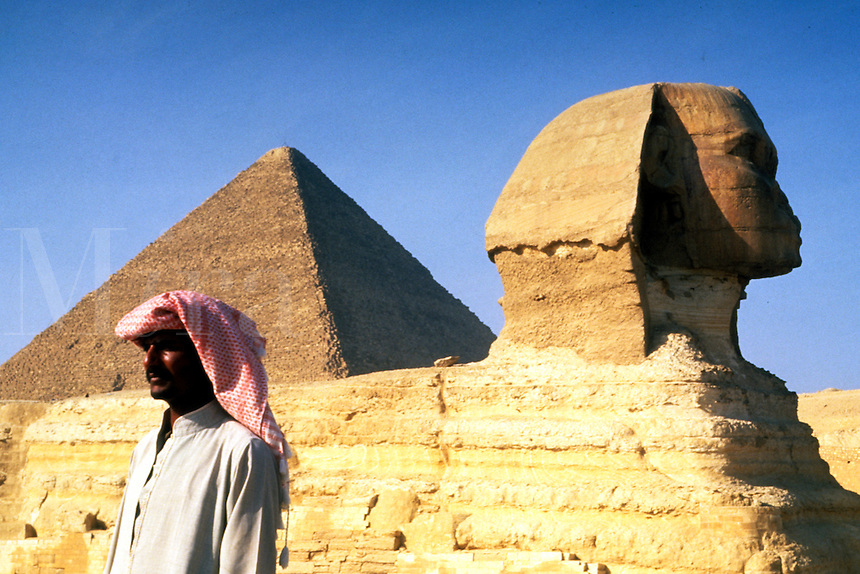 Close up of the famous Sphinx and the Pyramids of Giza in Egypt with local Arab man portrait