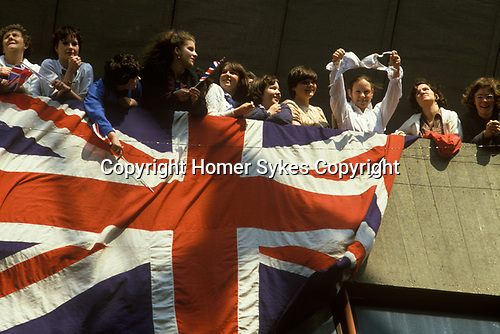 QE2 QEII Queen Elizabeth Second Southampton Dock. Leaves for the Falklands War, crowds of well wishers waive goodbye and wives of soldiers withUnion Jack flag and one girlfriend holding up her bra.