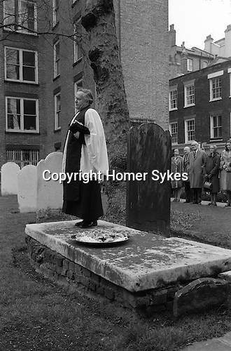 """Butterworth Charity, London England. 1976. StBartholemewtheGreat church, Good Friday.  The Rev'd Dr Newell Walbank.<br /> <br /> In 1887 John Butterworth created a trust to provide for poor widows of the parish. The trust was endowed with an investment of twenty-one pounds and ten shillings, and states that – """"On Good Friday in each year to distribute in the churchyard of St. Bartholomew the Great the sum of 6d. to twenty-one poor widows, and to expend the remainder of such dividends in buns to be given to children attending such distribution and he desired that the Charity intended to be thereby created should be called 'the Butterworth Charity'."""" <br /> <br /> Joshua Whitehead Butterworth was a member of a city firm of law publishers, and was perpetuating a charity dole that had been in existance for many years.  In 1887 the dividend from his endowment and other charitable doles was divided into 21 equal shares, and was placed on a flat tombstone in the churchyard, from which deserving and selected widows collected their Easter dole under the supervision of one of the churchwardens or a sidesman. No distribution of buns to children was made but each of the widows receives one or more buns. During the nineteenth century the sum distributed varied from year to year, but was ussually somewhere between two shillings and sixpence and four shillings.   <br /> <br /> Nowadays the choir and congregation meet for the traditional Easter service outside. The Rector preaches from the large flat tombstone in the centre of the churchyard, where once the widows collected their Easter dole. A silver plate contains hot cross buns. He enquires if there are any poor deserving windows in the congregation? Easter hymns are sung and afterwards hot cross buns are distributed to all present."""