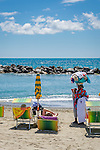 Italy, Liguria, Riviera Ligure di Levante, Moneglia: popular tourist resort - hawker offering clothes on the beach | Italien, Ligurien, Riviera Ligure di Levante, Moneglia: beliebter Urlaubs- und Badeort - fliegende Haendler  bieten am Strand Textilien an