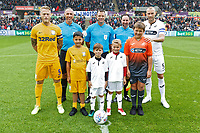 Referee James Linington (C) with his assistants, Tom Clarke of Preston North End (L)   and Mike van der Hoorn of Swansea City with children mascots during the Sky Bet Championship match between Swansea City and Preston North End at the Liberty Stadium, Swansea, Wales, UK. Saturday 11 August 2018