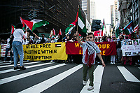 NEW YORK, NY - JUNE 15: A Pro-Palestine boy holds a flagpole next to the Empire State Building during a large protest in New York on June 15, 2021. The solidarity action of hundreds of pro-Palestinians is a form of support against the attacks carried out by the Israeli government. At the same time, Palestinian Prime Minister Mohammad Shtayyeh says the new Israeli government is just as bad as the old one and condemns Naftali Bennett's announcements in support of Israeli settlements. That is why the demonstrations continue in different parts of the world. (Photo by Pablo Monsalve / VIEWpress via Getty Images