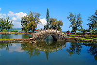 An arched stone bridge and Japanese pavilions decorate a lake at Queen Lili'uokalani Gardens, Hilo, Big Island.
