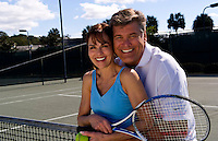 Attractive couple in their 50s relaxing at tennis courts after tennis in sunshine