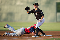Gavin Sheets (23) of the Kannapolis Intimidators waits for a pick-off throw as Aldrem Corredor (30) of the Hagerstown Suns dives back into first base at Kannapolis Intimidators Stadium on July 10, 2017 in Kannapolis, North Carolina.  The Suns defeated the Intimidators 8-5.  (Brian Westerholt/Four Seam Images)