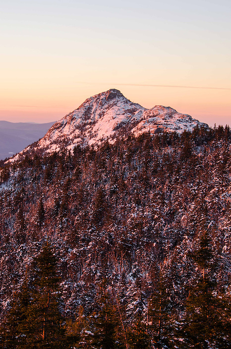 The warm hues of sunrise do little to combat the freezing winter conditions near the summit of Mt Chocorua.