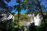 Beautiful Iguazu Falls cataracts, with green rainforest tree foreground and a rainbow across the rapids, in Iguacu National Park, Iguazu Brazil