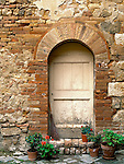 Tuscany, Italy   <br /> Arched door in a brick and stone wall with potted flowers and broom in a courtyard of the hill town of San Quirico d'Orcia