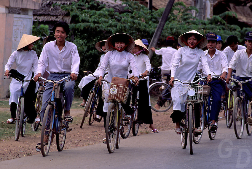 """Traditional Vietnamese Girls on their Bikes, circa 1992. Near Can Tho, the hub of the Mekong Delta (Vietnamese: Đồng bằng Sông Cửu Long """"Nine Dragon river delta""""), also known as the Western Region (Vietnamese: Miền Tây or the South-western region (Vietnamese: Tây Nam Bộ) is the region in southwestern Vietnam where the Mekong River approaches and empties into the sea through a network of distributaries. The Mekong delta region encompasses a large portion of southwestern Vietnam of 39,000 square kilometres (15,000sqmi). The size of the area covered by water depends on the season.<br /> The Mekong Delta has been dubbed as a """"biological treasure trove"""". Over 1,000 animal species were recorded between 1997 and 2007 and new species of plants, fish, lizards, and mammals has been discovered in previously unexplored areas, including the Laotian rock rat, thought to be extinct."""