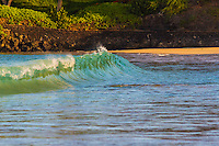 At sunrise, the green color of nearby palm trees is reflected in a small breaking wave, Kauna'oa Bay and Beach (a.k.a. Mauna Kea Beach), Big Island.