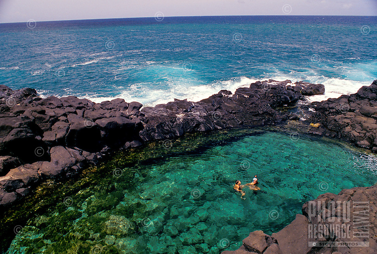 Couple snorkeling at queens bath on Kauai's north shore, near princeville