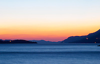Sunset over the sea. View over the islands Daksa and others. House lights. Dark blue sea. Uvala Sumartin bay between Babin Kuk and Lapad peninsulas. Dubrovnik, new city. Dalmatian Coast, Croatia, Europe.