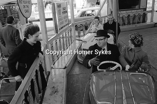 THE KINGS LYNN MART NORFOLK. 1974. Town hall dignitaries ride the dodgem bumper cars, free of charge after the opening ceremony.<br /> The first recorded Charter granted to the town was in 1204. However the Charter marking the Valentine's Day fair was granted by Henry VIII in 1537. <br /> The site of the fair is the Tuesday Market Place with the Mayor and Chairman of the Markets Committee accompanied by local dignitaries and officials of the Showmen's Guild performing an opening ceremony. <br /> A town hall official takes a turn on the Dodgem Bumper cars. This Valentines day fair is traditionally the first showman's fair of the year.