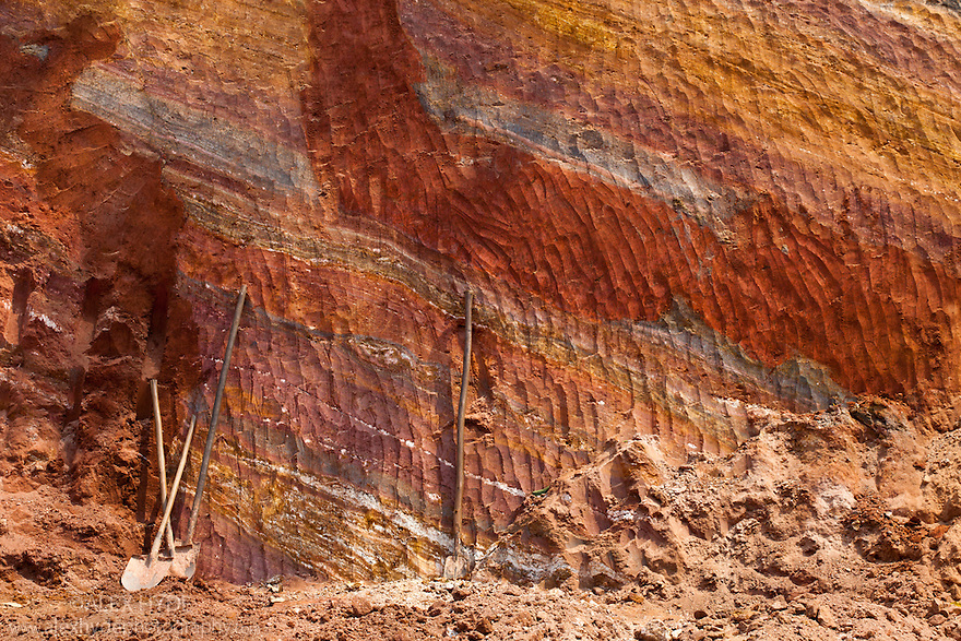 Clay deposits visible as distinct layers, exposed after roadside excavation, with workers' tools included for scale, Andasibe-Mantadia National Park, Madagascar.